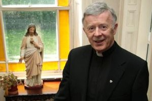 Priest standing next to a statue.