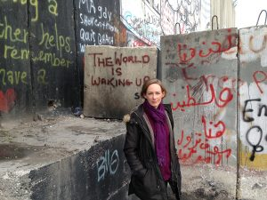 Woman standing in front of a wall marked with graffiti