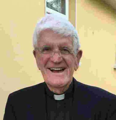 Elderly priest smiling at the camera.